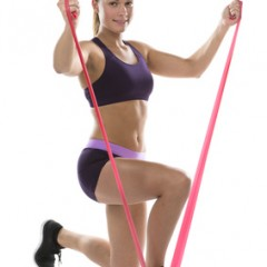 Young woman working out with exercise bands or straps to tone and strengthen her muscles kneeling down anchoring it with her foot, isolated on white